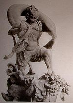 Fūjin. Three-quarter view of a statue. His left leg is bend as if climbing stairs and he is carrying a long bag-shaped object which goes from one shoulder to the other around the back of his head. Black and white photograph.