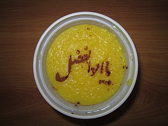 Stencil - Writing an Arabic phrase by stencil and cinnamon powder on Iranian dessert, Sholezard.