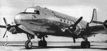 Close-up, in black-and-white, of a silver-bodied four-engined propellor aircraft standing on an apron at an airport