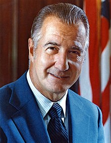 Spiro Agnew in 1972, a middle-aged white American male in suit and tie, standing in front of a furled flag