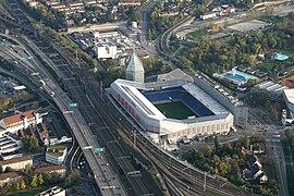 Vue aérienne d'un stade de football portant l'inscription « BASEL.CH » entouré de bâtiments, de voies de chemin de fer et d'une autoroute