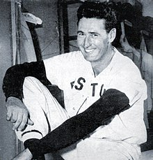 "A man, wearing a white baseball uniform with the words ""BOSTON"" across his chest obscured, smiles towards the left."