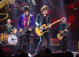 Rolling Stones performing on stage in Milwaukee, Wisconsin. From left: Charlie Watts on brown drum set, Ronie Wood wearing a purple jacket with black jeans playing a silver coloured guitar, Mick Jagger wearing black shirt and pants playing an orange/yellow guitar, Keith Richards with a green vest and black clothing playing an orange/yellow guitar (similar to Jagger's)