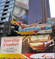 An advertisement in Times Square for travel on the Boeing 777-200LR from New York City to Mumbai