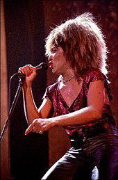 A woman holding onto a microphone and wearing leather a necklace, a sparkly red-colored top, and leather pants.