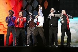 Six men dressed in variously colored clothes performing on a stage.