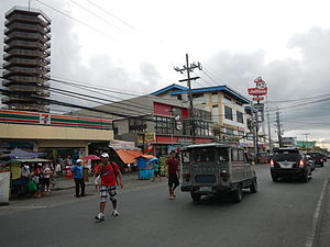 Trece Martires - A 7-Eleven and Jollibee along Trece Martires-Indang Road. Steel tower from Trece Tower Mall and Parkson City (Formerly L-Paseo) is also seen on the background.