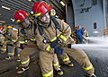U.S. Navy Petty Officer 3rd Class Jordan Crouse aims a fire hose on a simulated fire during a general quarters drill aboard the amphibious assault ship USS Iwo Jima (LHD 7) as the ship operates in the Gulf of Aden 121017-N-OR551-040.jpg