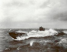 A black and white image of a submarine breaking through a wave in rough water.