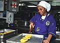 US Navy 030418-N-9741A-007 Mess Management Specialist 3rd Class Stacey Davis from New York, N.Y. moves chicken patties from the baking pan to a serving dish.jpg