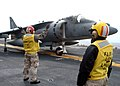 US Navy 040317-N-6920A-003 Aviation Boatswain's Mate 3rd Class Keith Hawkins, of Sedalia, Mich., stands-by to assist Chief Aviation Boatswain's Mate Agustus Jones, of Brooklyn, N.Y., in launching an AV-8B Harrier jump jet off t.jpg