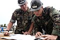 US Navy 040708-N-0683J-020 Builder 1st Class Troy Hanegmon and Steelworker 2nd Class Carl Hillier assigned to Naval Construction Battalion Unit (CBU) 421 discuss the blue prints.jpg