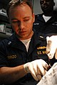 US Navy 070315-N-7945K-090 Lt. Nathan Perrizo, a medical officer attached assigned to USS Nassau (LHA 4) stitches a head wound.jpg