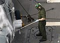 US Navy 080217-N-7446H-034 Aviation Ordnanceman 2nd Class Jason Barcellos sprays soap on an SH-60B Seahawk helicopter attached to Helicopter Antisubmarine Squadron Light (HSL) 51 on the flight deck of the Arleigh Burke-class gu.jpg