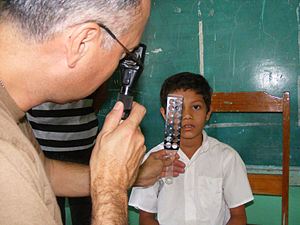 United States Navy Reserve - U.S. Navy optometrist Cmdr. Louis Perez uses a retina scope and lens rack to check the eyes of 9-year old Sergio Colochos during the Beyond the Horizon humanitarian assistance exercise in Honduras.
