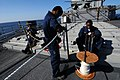 US Navy 100130-N-1688B-088 Boatswain's Mate Seaman Rutchal Mandafe, Seaman Moses Young and Boatswain's Mate Seaman Daven Arce splice a line on the missile deck of the guided-missile cruiser USS Hue City (CG 66).jpg