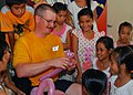 US Navy 100813-N-3589B-016 Master-at-Arms 1st Class Jonathan D. Baker makes balloon animals for Vietnamese children during a community service project at the Village of Hope orphanage.jpg