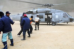 US Navy 110315-N-IC111-121 Naval Air Crewman 2nd Class Zack DelCorte hands bottled water to a Japanese citizen.jpg