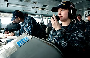 US Navy 111211-N-OY799-048 Operations Specialist Seaman Apprentice Michell Prom, from San Diego, receives reports from lookouts on the bridge aboar.jpg