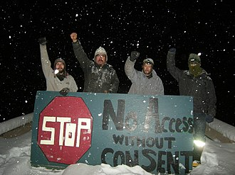 Unist'ot'en Camp - Members of the Unistoten Camp behind a check-point sign. The sign reads: No access without consent.