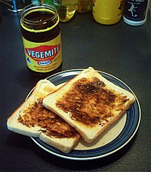 Slices of pale bread covered with a thick, dark brown spread; a jar filled with the spread is labelled: Vegemite