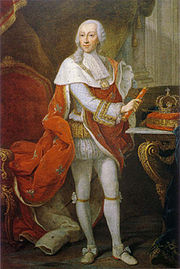 Full-length portrait of a bewigged monarch in white tights and a red robe with his crown sitting on a table