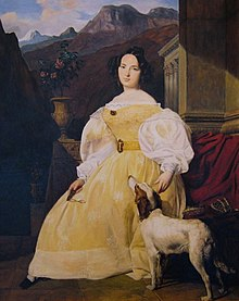 A woman with short black hair arranged in curls is wearing a yellow dress. She is seated with one hand resting on a dog's head, the other holding a pair of glasses.