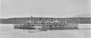 Photograph of steamship from the side showing the whole ship as it steams along a very calm river with flags hoisted and three decks populated with riders.