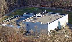 A large light-colored building with a flat roof seen from above, surrounded by bare trees.