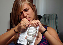 A girl is attempting to open a plastic package containing a light bulb.