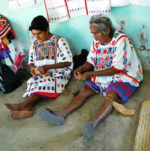 Amuzgo textiles - Amuzgo women dressed in huipils preparing thread for weaving
