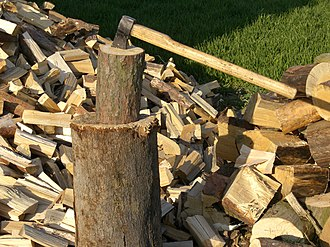 Firewood - Stack of split firewood and a maul for splitting, Czech Republic