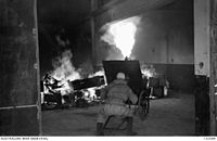 132594 A JAPANESE WORKMAN WEARING A GAS-MASK DIRECTS JETS FROM A MOBILE FLAME-THROWER TOWARDS THE PILE OF GASOLINE-SOAKED DEBRIS INSIDE THE BUILDING AND WITHIN A MATTER OF SECONDS THE INTERIOR OF THE BUILDING WAS A RAGING INFERNO.JPG
