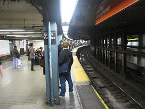 14th Street–Union Square (New York City Subway) - Downtown platform for the local services (left) and express services (right), showing the curvature of the station and the movable platforms