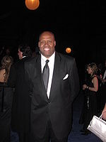 Craig Robinson is smiling for the camera while attending a very formal ball. He is wearing a dark black suit that has visible grey-colored lines running vertically through it. His white undershirt is complemented by a shiny, solid black tie.