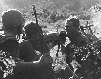 Operation Double Eagle - Marine machine gun is fired over the shoulder of assistant gunner to clear dense foliage