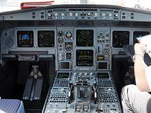 Кабина А330.  Все приборы и дисплеи включены.  Два сиденья занимают обе стороны кабины, разделенные центральной консолью.