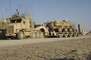 Tractor unit - An Oshkosh M1070 8×8 Heavy Equipment Transporter (HET) tractor pulling a 5-bogie M1000 HETS trailer, carrying a slat-armored M93 Fox 6×6 NBC detection vehicle near Baghdad