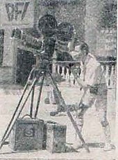 A man with short hair and a white shirt is controlling a large camera. He is facing left.