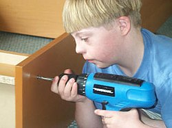 A boy with Down syndrome using cordless drill to assemble a book case.jpg