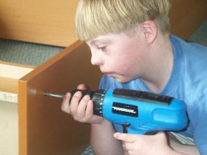 A Caucasian adolescent male with Down syndrome dressed in a blue t-shirt is holding a blue and black electric drill with both hands. He is using it to assemble a wooden, flat-pack style bookcase.