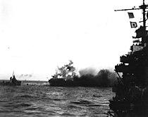 A heavy explosion on board USS Lexington (CV-2) blows an aircraft over her side, 8 May 1942 (80-G-7413).jpg