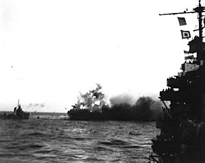 A heavy explosion on board USS Lexington (CV-2) blows an aircraft over her side, 8 May 1942 (80-G-7413).jpg