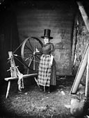 "A woman in ""Welsh national"" dress with a spinning wheel NLW3361179.jpg"