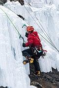 Un grimpeur escaladant une cascade de glace avec piolets et crampons