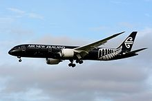 A mid-size jet airliner in flight. The plane livery is all-black and features a New Zealand silver fern mark.