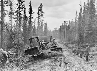 Alaska Highway - A caterpillar tractor with grader widens the roadway of the Alaska Highway, 1942