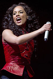 The photo shows an African American female with medium brown hair with her head tilted to her right with her mouth open. She is wearing a red sleeveless shirt with dark wash colored jeans and is holding a microphone with her right hand.