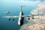An air-to-air front view of a C-5B Galaxy aircraft of the 22nd Military Airlift Squadron, foreground, and a -C-141B Starlifter- aircraft from the 86th Military Airlift Squadron- in formation over San Francisco DF-ST-88-07446.jpg