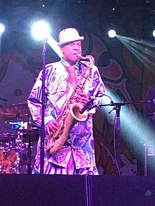 Angelo Moore in a white bowler hat playing a saxophone